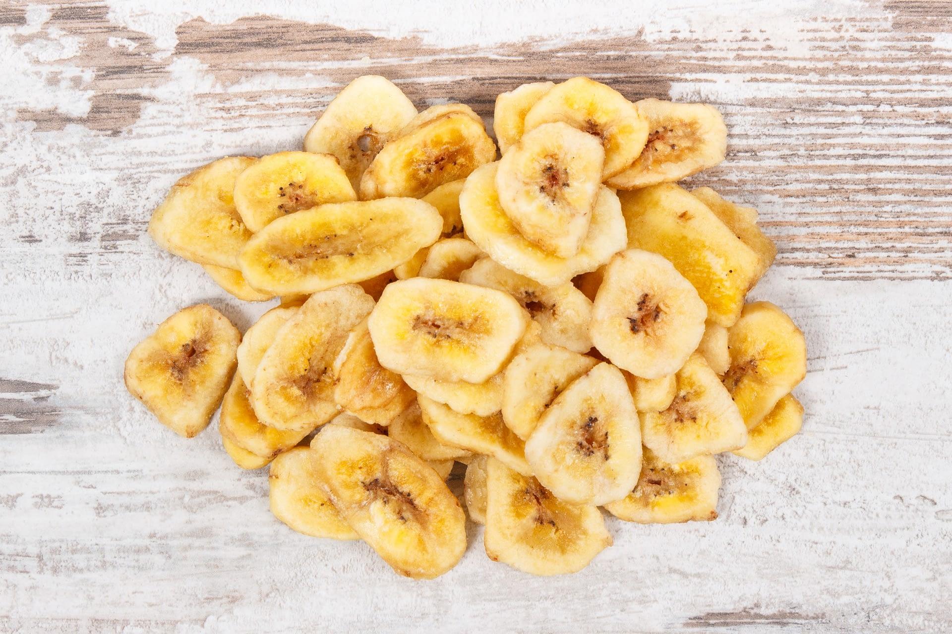 Dried organic banana chips on rustic board